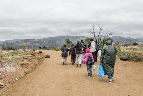 Refugees and migrants walking the dusty road in the rain to the reception center of Presevo, Serbia